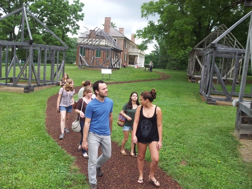 Walking through the interpretive landscape around the mansion, past wooden frames that represent the location of quarters for enslaved servants.